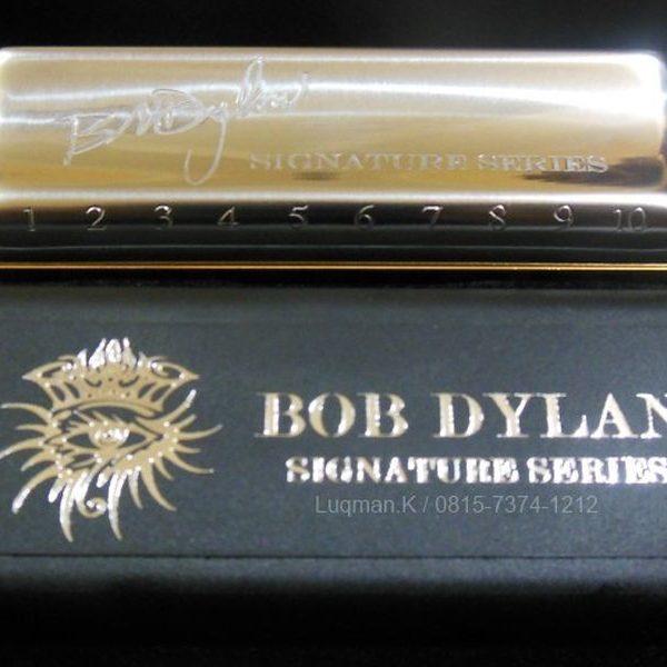 """Harmonica Diatonic Hohner Signature Bob Dylan piringan penutup khas Bob Dylan, logo """"Eye"""" Dylan, dan dilengkapi dengan foto Dylan di dalam penutupnya."""